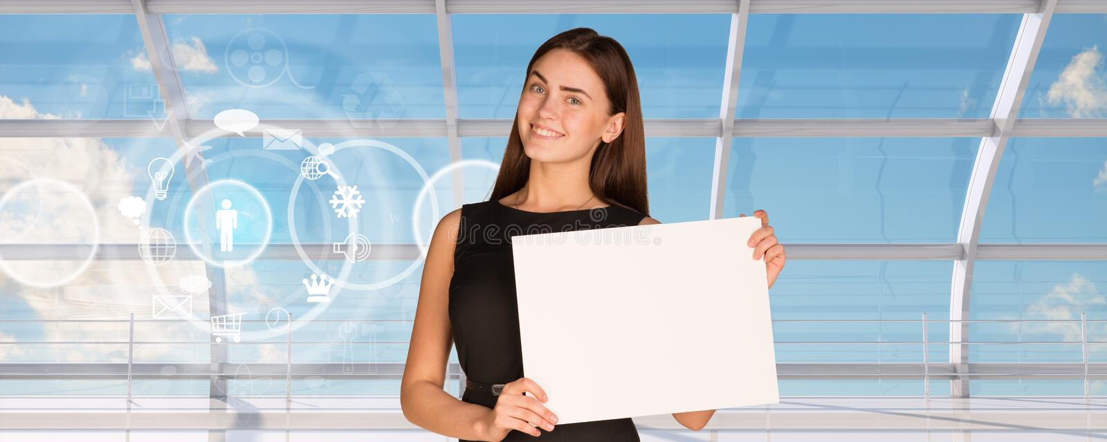 Smiling young businesswoman holding blank paper royalty free stock image