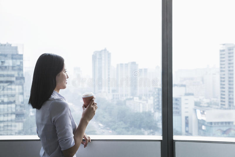 Smiling young businesswoman holding a coffee cup and looking out the window a the cityscape in Beijing, China stock photography