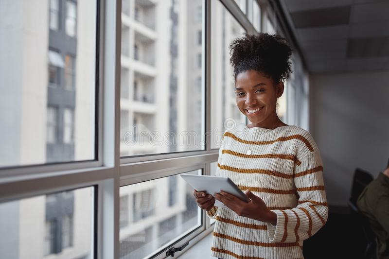 Portrait of an attractive young african american businesswoman with digital tablet standing in front of windows at royalty free stock photo