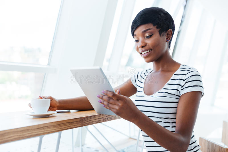 Smiling young businesswoman holding tablet and drinking coffee royalty free stock photo