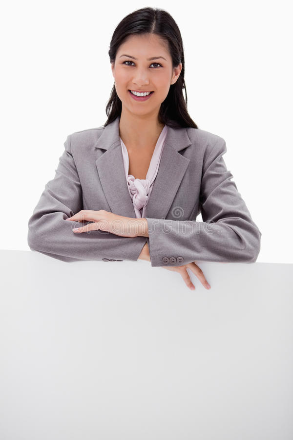 Download Smiling Young Businesswoman Leaning On Blank Wall Stock Image - Image: 22664979