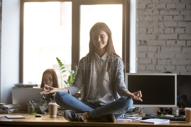 Smiling young businesswoman meditating, practicing yoga on office desk stock photo