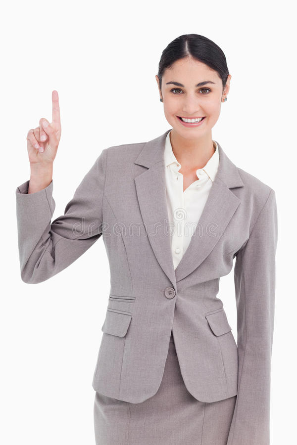 Smiling young businesswoman pointing up stock photo