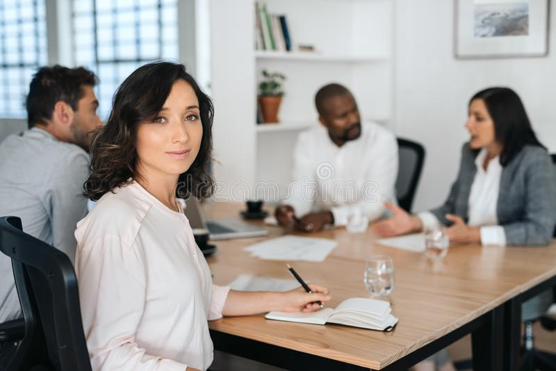 Smiling young businesswoman sitting with colleagues in a boardroom stock images