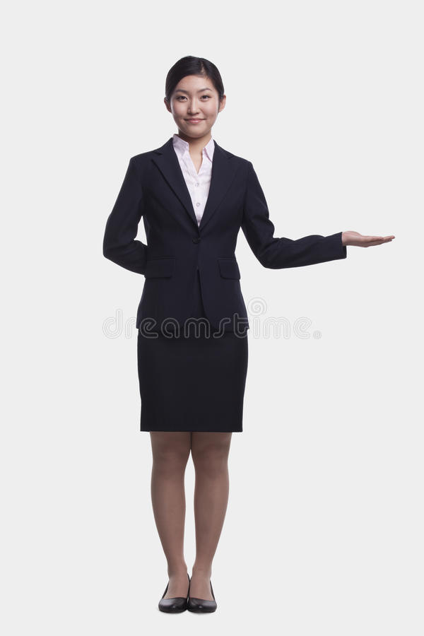 Smiling young businesswoman standing with her hand out, full length studio shot stock photography