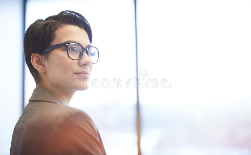 Smiling Young Businesswoman Standing by Window stock photos