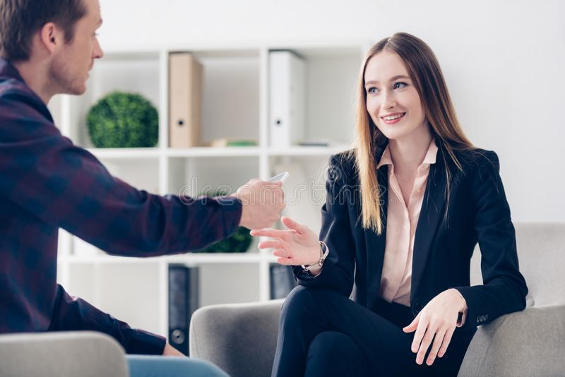 Smiling young businesswoman in suit giving interview to journalist. In office stock images