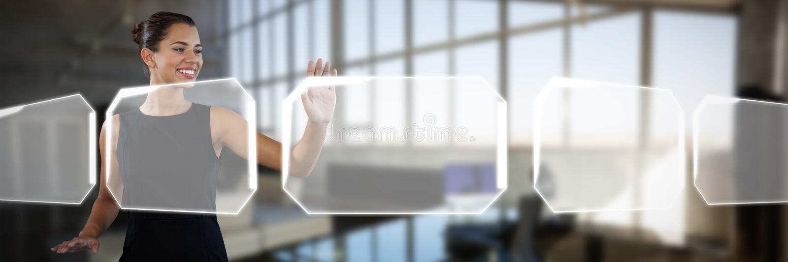 Smiling young businesswoman using invisible interface against interior of empty creative office royalty free stock photos
