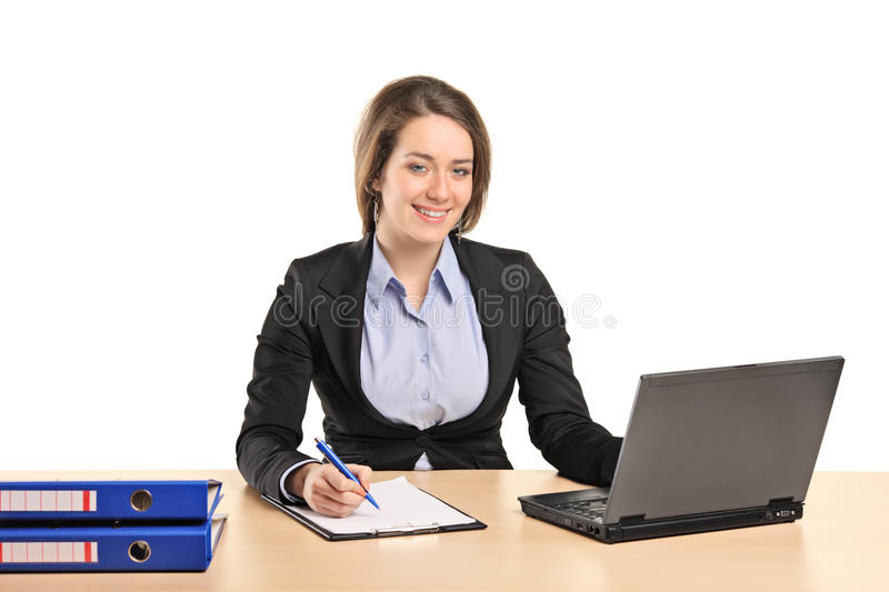 A smiling young businesswoman working on a laptop