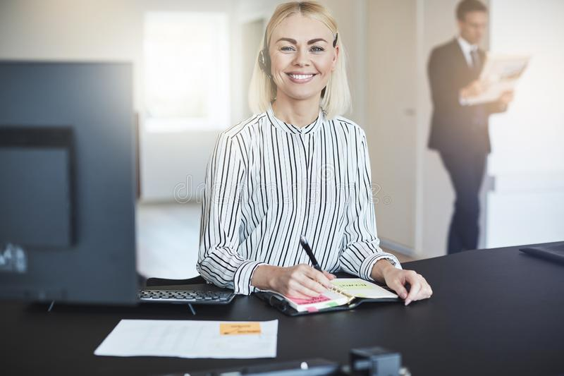 Smiling young businesswoman writing in her day planner at work royalty free stock image