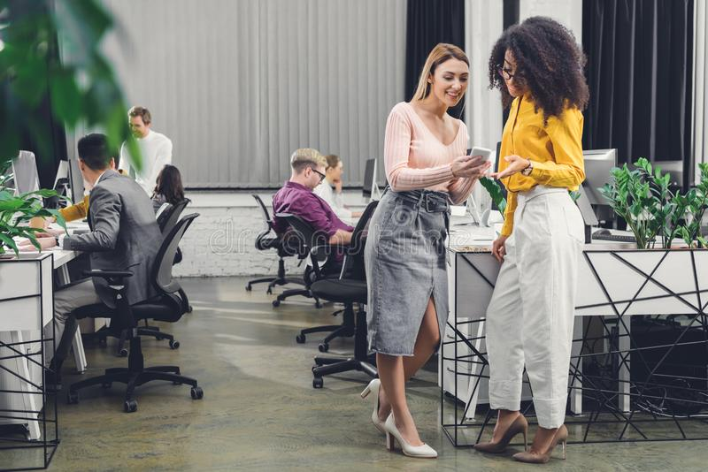 Smiling young businesswomen using smartphone and talking while colleagues working behind. In office stock photo