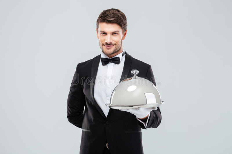 Smiling young butler holding tray with silver catering dome stock photo