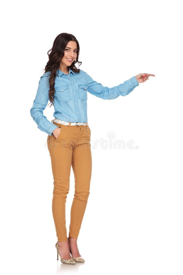 Smiling young casual woman potingin finger to side royalty free stock photo
