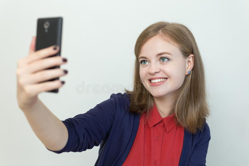 Smiling young caucasian girl woman taking selfie or making a video call on mobile phone stock images