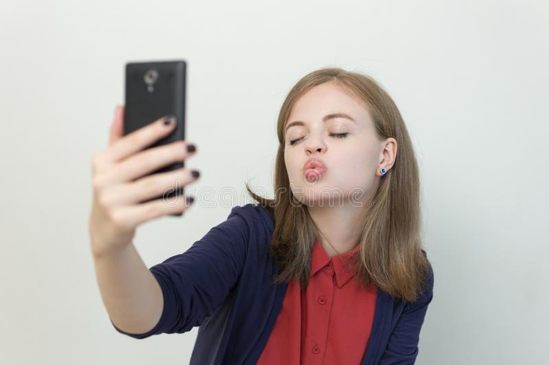Smiling young caucasian girl woman taking selfie or making a video call on mobile phone stock photo
