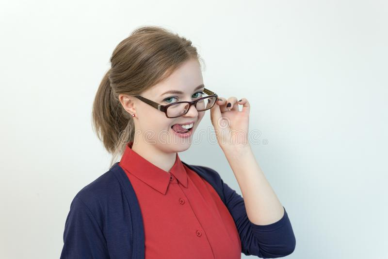 Smiling young caucasian girl woman wearing glasses in the office, flirting royalty free stock photography