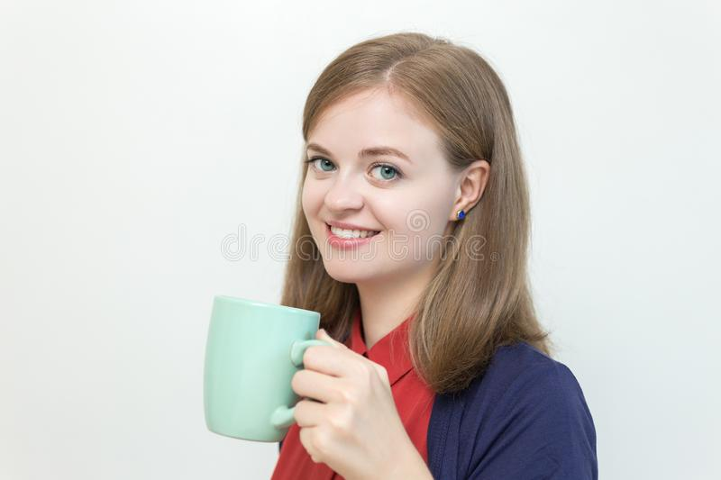 Smiling young caucasian woman girl holding a mug cup of coffee. Good morning! royalty free stock photo