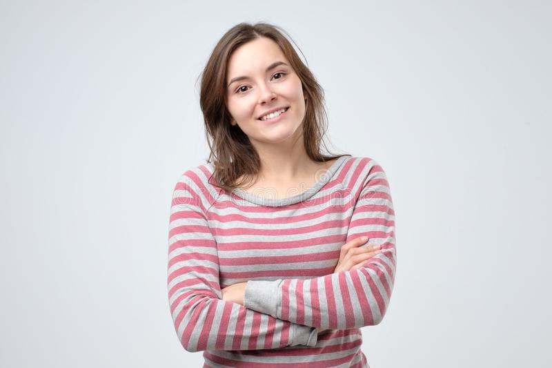 Smiling young caucasian woman with her arms folded stock photos