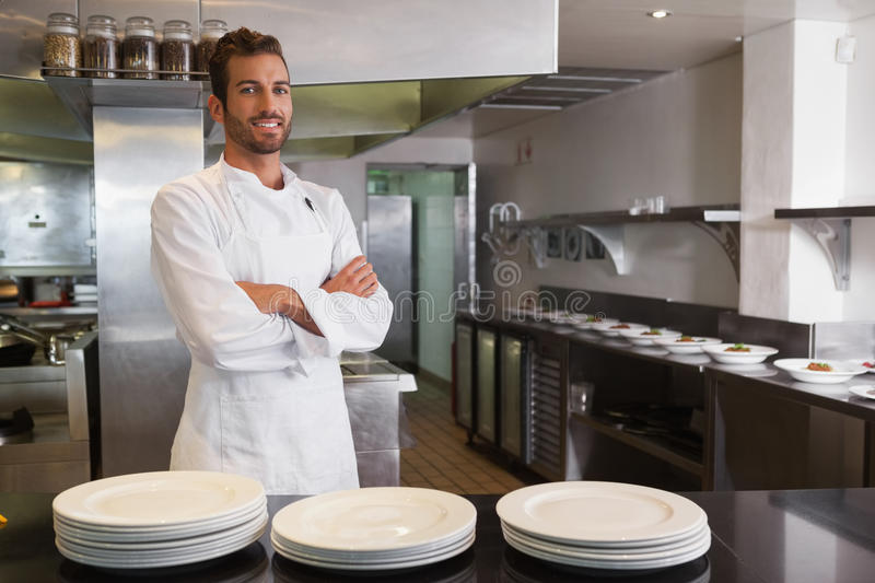 Smiling young chef standing with arms crossed behind counter. In a commercial kitchen stock photos