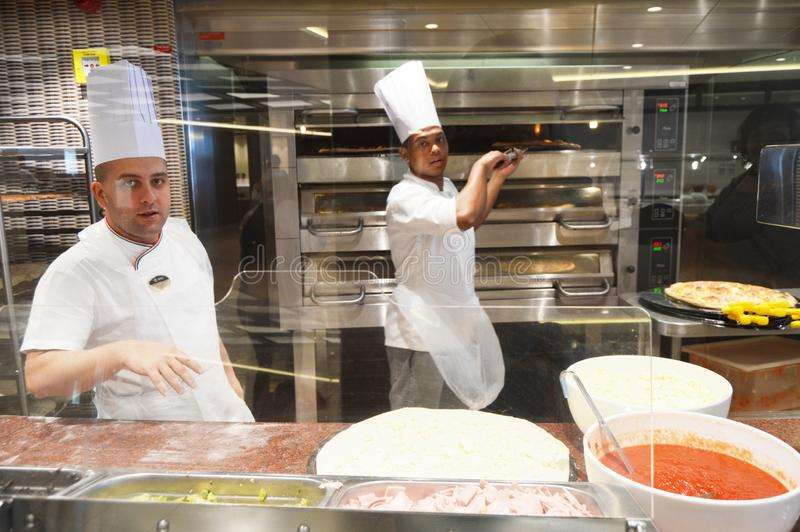 Smiling young chef in a white uniform serves traditional Italian pizza on a cruise liner MSC Meraviglia. 10 October 2018 stock photo