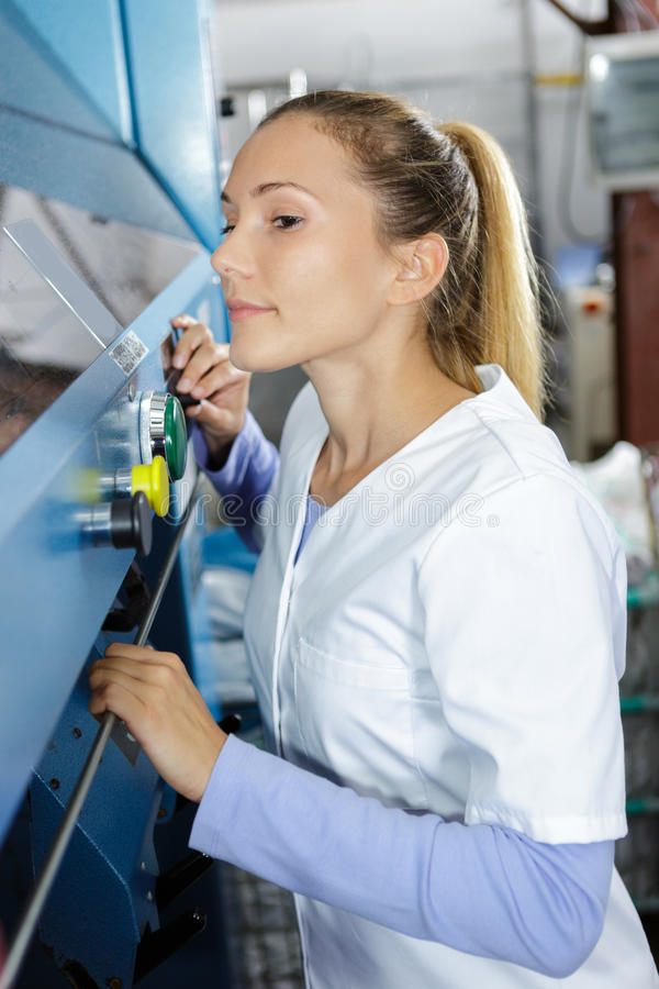 Smiling young chemist using machine in laboratory royalty free stock photography