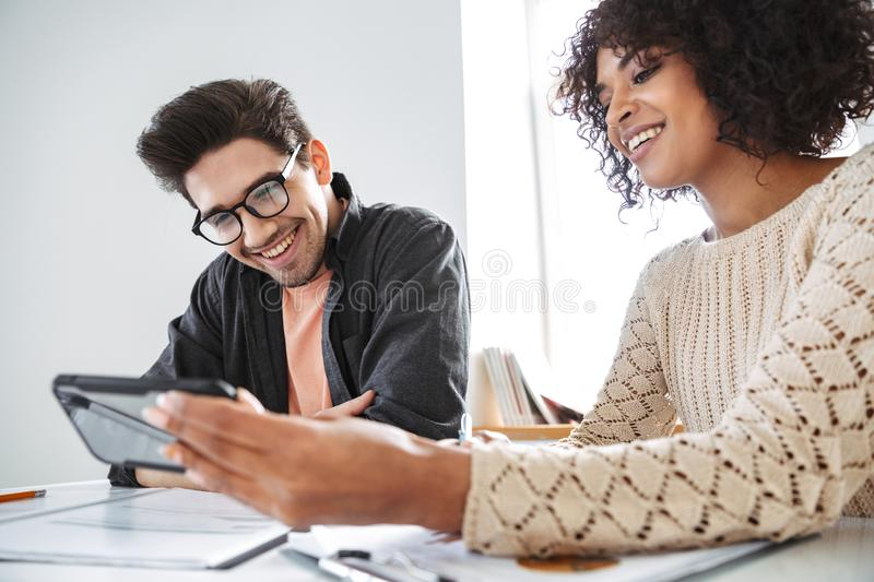 Smiling young colleagues using smartphone together royalty free stock image