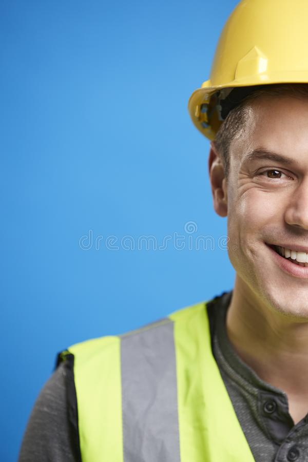 Smiling young construction worker in hard hat, vertical crop stock photography
