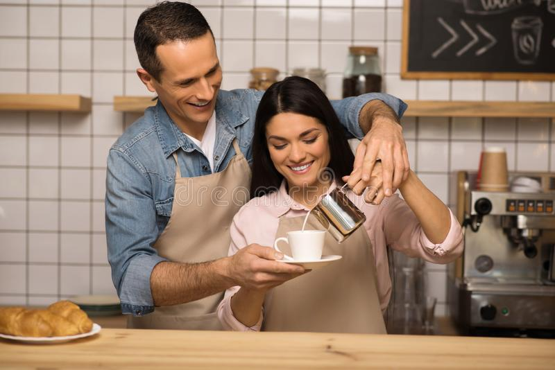 Couple in aprons preparing coffee. Smiling young couple in aprons preparing coffee together in cafe royalty free stock photos