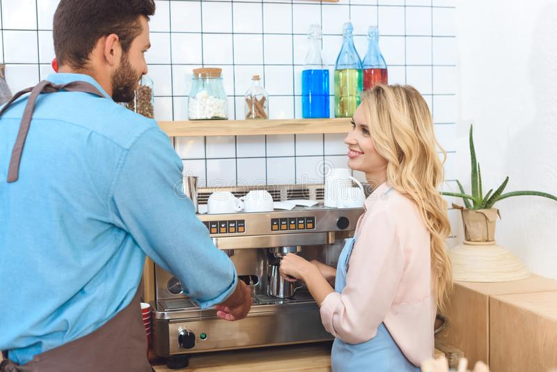 Smiling young couple of cafe workers making coffee together and using. Coffee machine stock photography