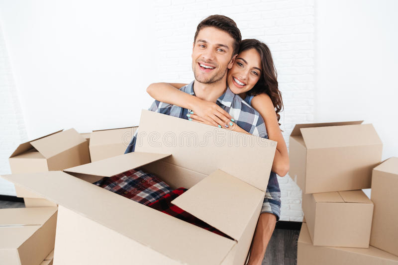 Smiling young couple carrying cardboard boxes and hugging royalty free stock images