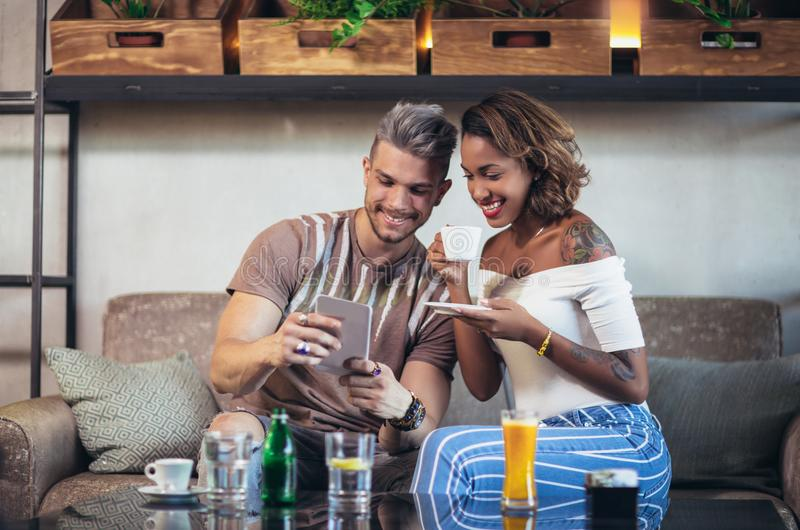 Smiling young couple in a coffee shop using touch screen computer stock images