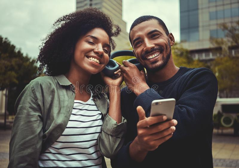 Smiling young couple enjoying listening to music on one headphone stock images