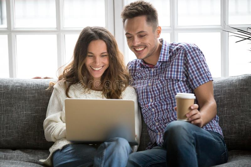 Happy couple laughing looking on laptop screen sitting on sofa. Smiling young couple enjoying morning coffee with computer sitting on sofa at home together royalty free stock photo
