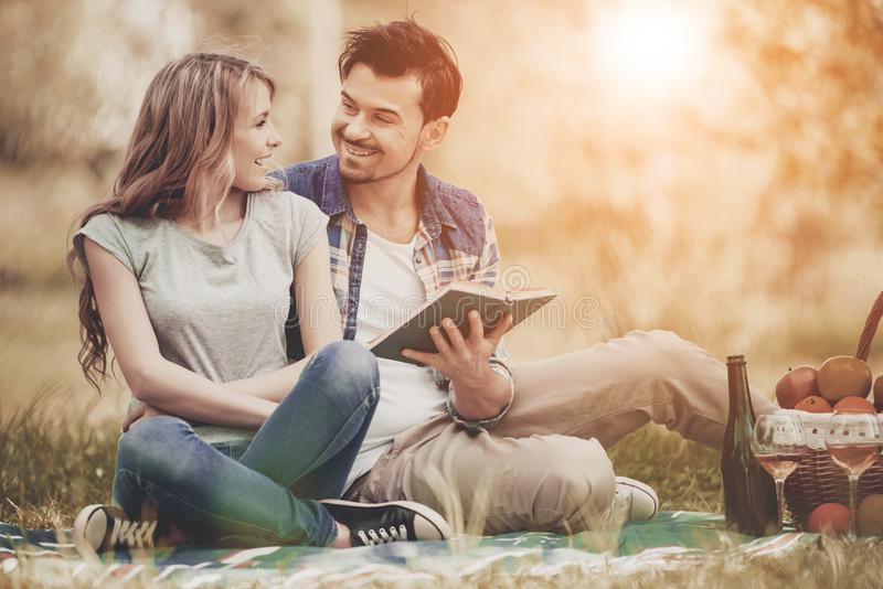 Couple Lying on Grass and Drink Wine in Park. stock image