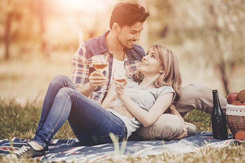 Couple Lying on Grass and Drink Wine in Park. royalty free stock image