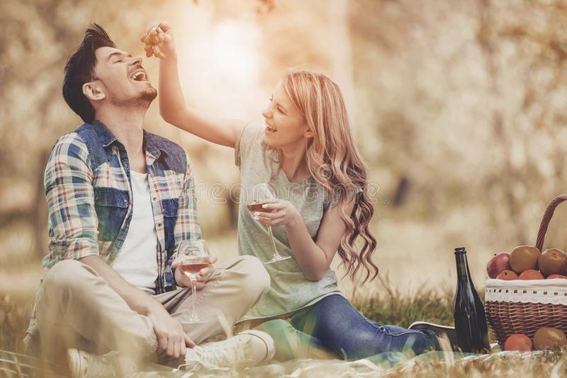 Couple Lying on Grass and Drink Wine in Park. stock photo
