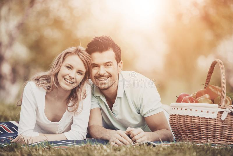 Young Couple Lying on Green Grass in Summer Park. stock image