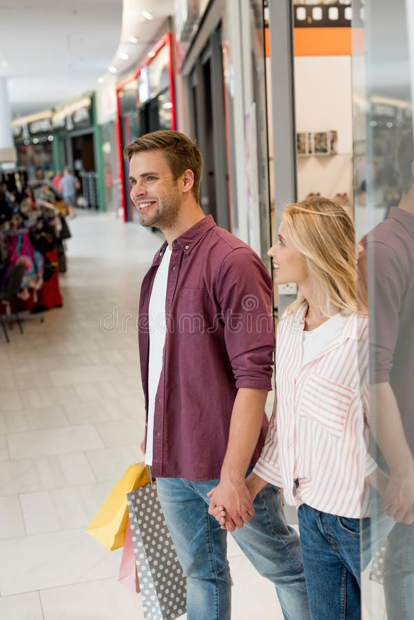 smiling young couple with paper bags walking out from store at shopping stock images