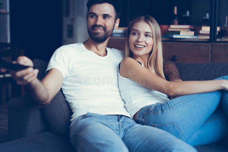Smiling young couple relaxing and watching TV at home. royalty free stock photos