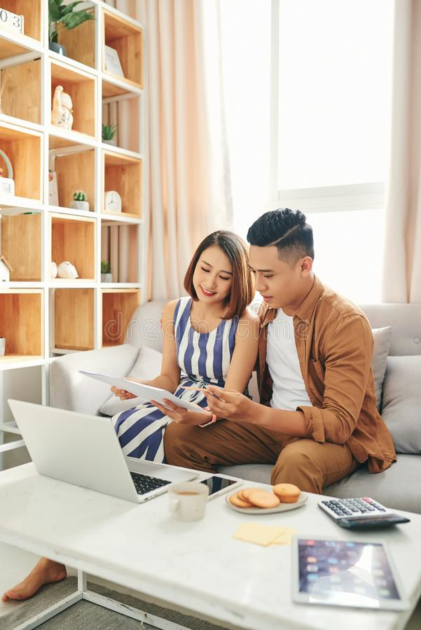 Smiling young couple sit on couch using laptop taking care of utility bills and house, read paperwork royalty free stock photography