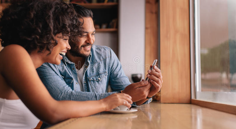 Smiling young couple sitting at coffee shop looking at mobile ph royalty free stock photos