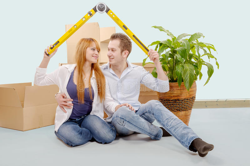 Smiling young couple sitting after moving house royalty free stock images