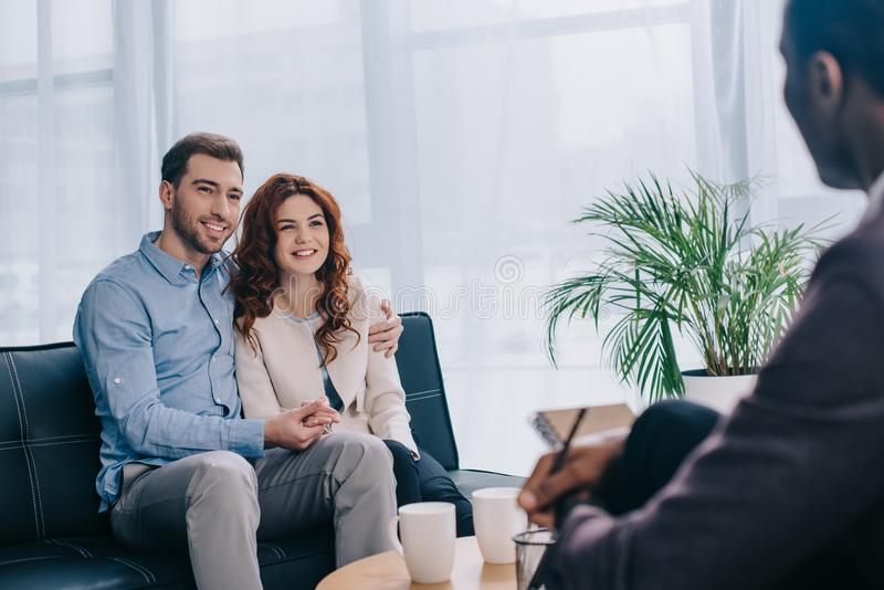 Smiling young couple sitting on sofa and talking to counselor with pencil royalty free stock image