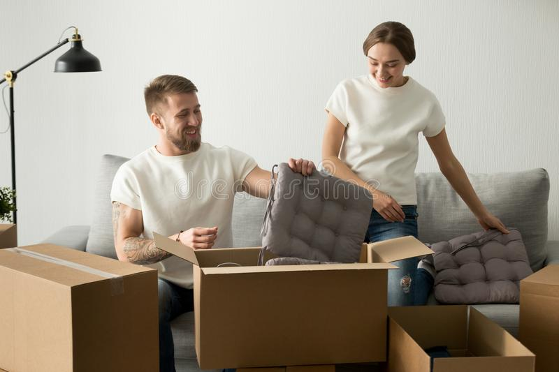Smiling couple unpacking cardboard boxes with belongings royalty free stock photography
