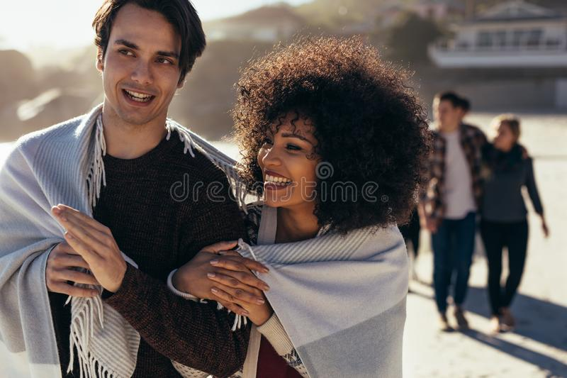 Smiling young couple walking on the beach royalty free stock image