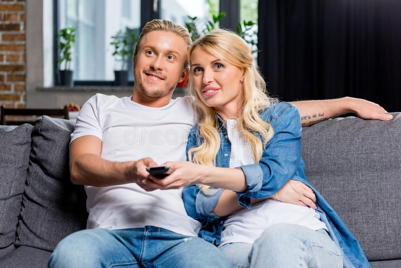 Smiling young couple watching tv together. At home stock photography