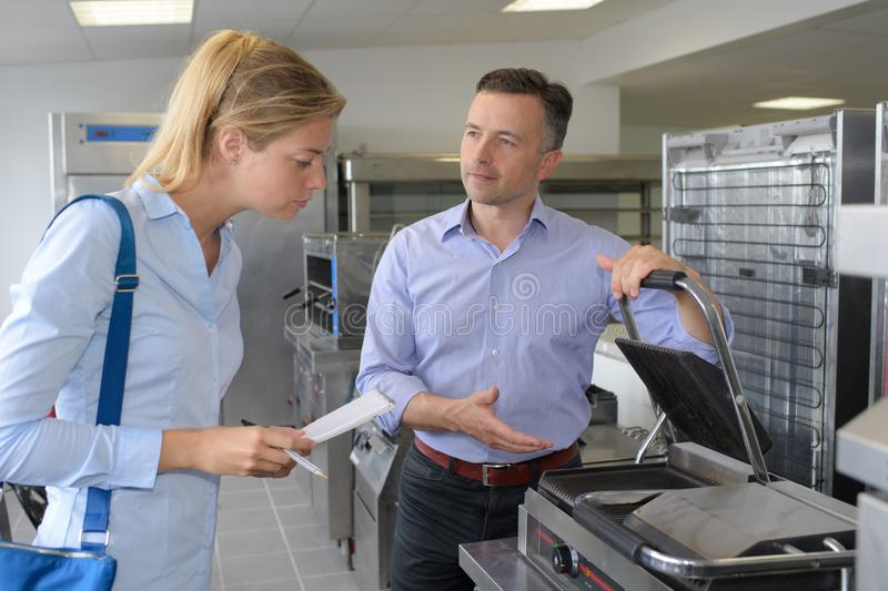 Smiling young customers purchasing toaster in domestic appliances section royalty free stock photography
