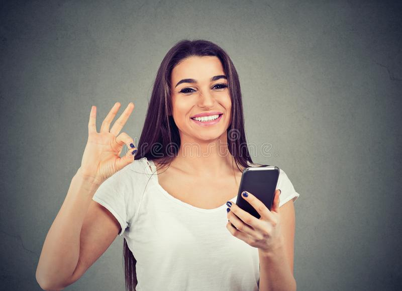 Smiling young cute woman holding blank screen mobile phone and showing ok sign royalty free stock image