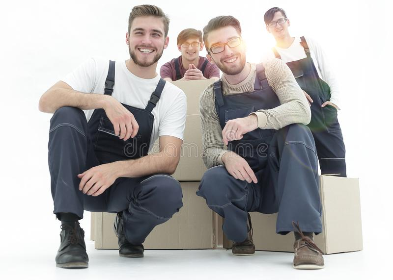 Smiling young delivery men holding stack of boxes. Isolated on w. Men with stacked boxes isolated on white stock images