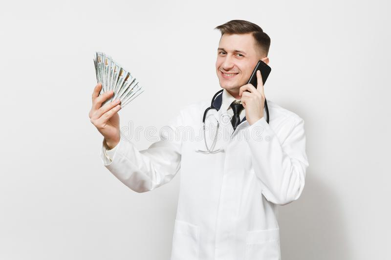 Smiling young doctor man isolated on white background. Male doctor in medical uniform talking on mobile phone, holding. Bundle of dollars, banknotes, cash money royalty free stock photo